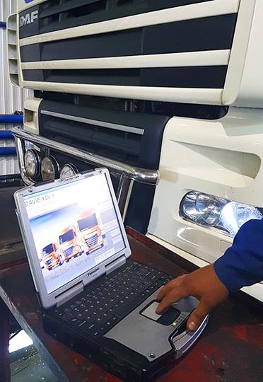Специалист станции ТО проводит компьютерную диагностику тягача